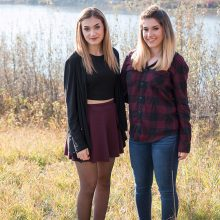 2 sisters smiling outside by the river photo by Candice Vera Photography - Lifestyle and Family Photography