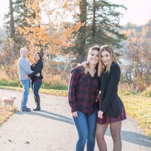 2 sisters hugging with parents hugging in the background photo by Candice Vera Photography - Lifestyle and Family Photography