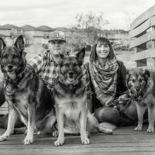 man and woman sitting on a bridge deck with their 3 dogs photo by Candice Vera Photography - Lifestyle and Family Photography