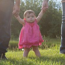Baby girl in bright pink dress hanging on to mom and dad as she walks photographed by Candice Vera Photography
