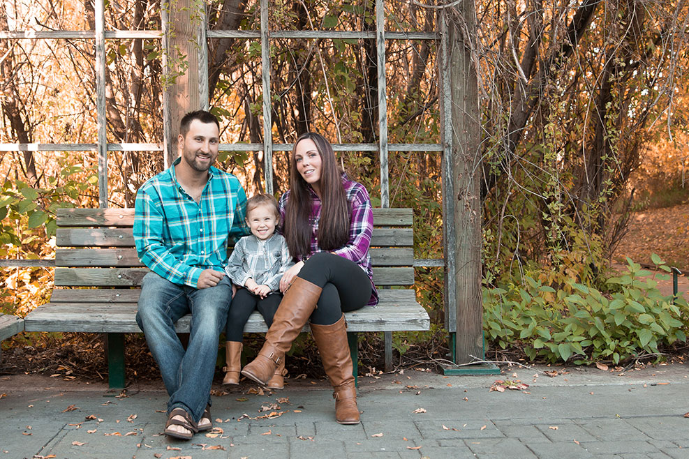 Parents sitting on a bench with young daughter photo by Candice Vera Photography - Lifestyle and Family Photography