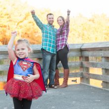 young girl dressed in supergirl costume as parents look on photo by Candice Vera Photography - Lifestyle and Family Photography