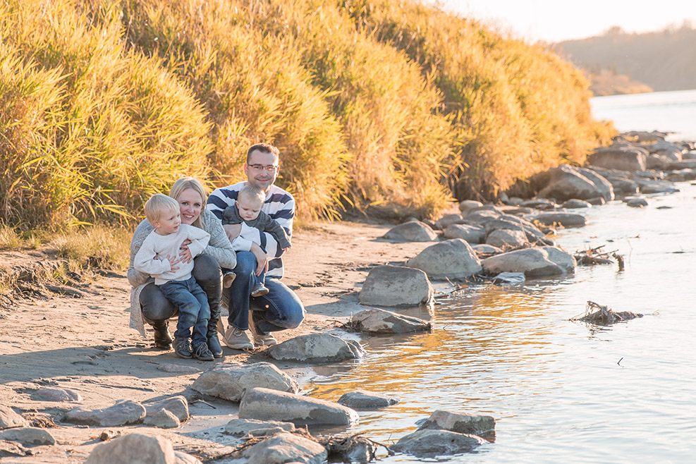 Young family of 4 by the rivers edge photo by Candice Vera Photography - Lifestyle and Family Photography