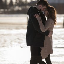 Tender moment between man and woman in snowy field photo by Candice Vera Photography - Weddings and Engagements Photography