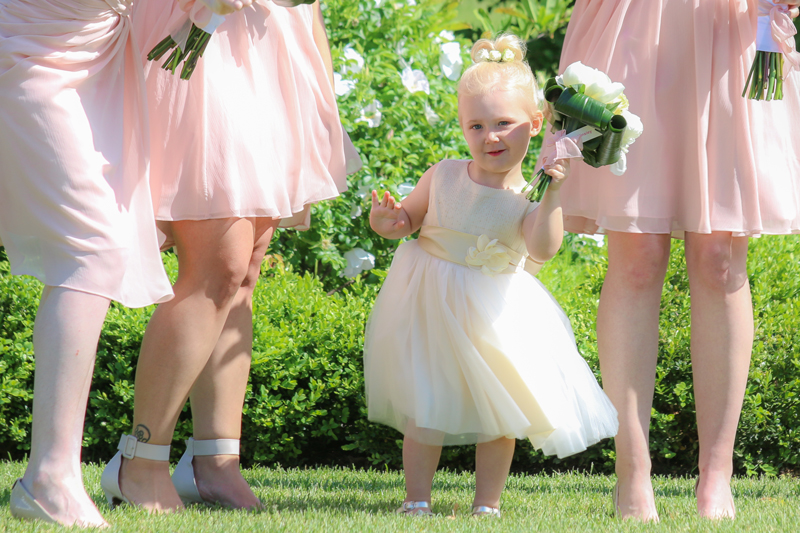 Flower girl holding up her bouquet while bridesmaids look on photo by Candice Vera Photography - Weddings and Engagements Photography