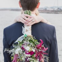 bride hugging groom with her bouquet on his back photographed by Candice Vera Photography