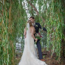 Young bride and groom kissing in the weeping willow trees photographed by Candice Vera Photography