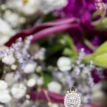 closeup of the brides wedding ring with purple flowers in the background photographed by Candice Vera Photography