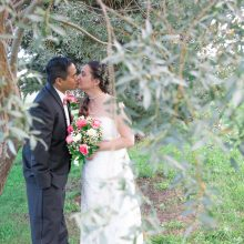 Bride holding bouquet of pink and white roses kisses her groom by willow tree photographed by Candice Vera Photography