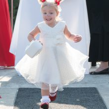 Flower girls smiling as she runs down the aisle photographed by Candice Vera Photography