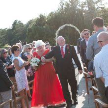 Bride in red dress and groom walking down the aisle photographed by Candice Vera Photography